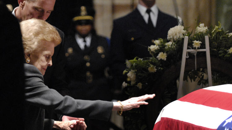 FILE - In this Monday, Jan. 1, 2007 file picture, Betty Ford reaches out to touch the casket of her husband former President Gerald Ford in the Rotunda of the U.S. Capitol in Washington. Behind her is her son Steve Ford. Betty Ford, the former first lady whose triumph over drug and alcohol addiction became a beacon of hope for addicts and the inspiration for her Betty Ford Center, has died, a family friend said Friday, July 8, 2011. She was 93. (AP Photo/Nick Wass, Pool)