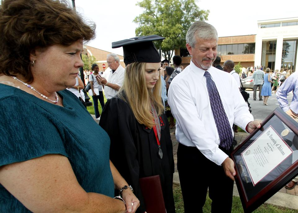 Vega Sigler, Brooke Lofton, and Allan Sigler look at the diploma for Morgan Sigler on Saturday, Aug. 6, 2011 in Tuscaloosa, Ala.  Morgan lost her life when a tornado ripped through Tuscaloosa on April 27, 2011. (AP Photo/Butch Dill)