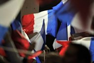"Supporters wave French flags during a campaign meeting of incumbent President Nicolas Sarkozy in the southwestern city of Avignon. Sarkozy and his supporters believe that he is relentlessly targeted by ""biased"" left-wing media"