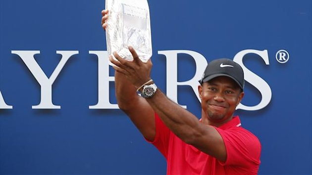 Tiger Woods lifts The Players Championship trophy in the air after winning the PGA golf tournament at TPC Sawgrass (Reuters)