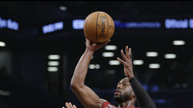 Miami Heat guard Dwyane Wade (3) shoots over Brooklyn Nets center Brook Lopez (11) in the first half of an NBA basketball game Wednesday, Jan. 30, 2013, in New York. (AP Photo/Kathy Willens)