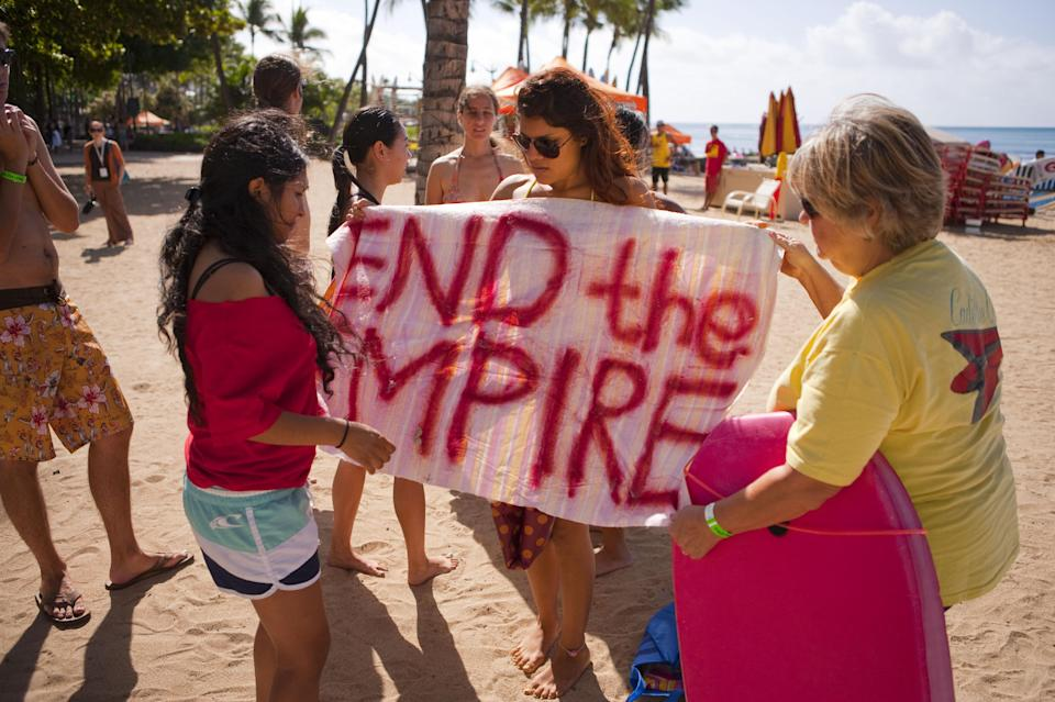 A group of protesters prepare their signs before heading out into the ocean to hold an anti-APEC protest at Waikiki Beach in Honolulu on Saturday, Nov. 12, 2011 as the summit is held in Oahu over the weekend. (AP Photo/ Marco Garcia)