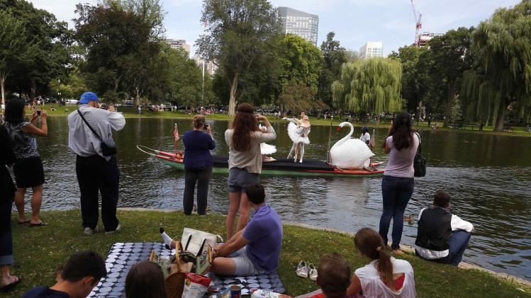 "Dancers from Boston Ballet ride a swan boat on the pond in the Public Garden past picnickers onshore, ahead of the company's performances of the ballet ""Swan Lake,"" in Boston"