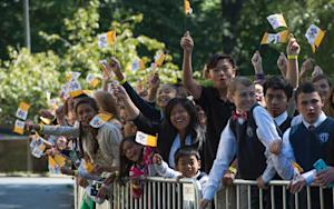 School children and parents cheer while waiting for…