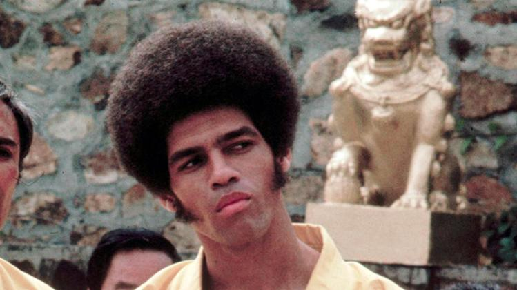 "This 1973 photo released by Warner Bros. Entertainment shows Jim Kelly as Williams in a scene from ""Enter the Dragon."" Kelly, who played a glib American martial artist in ""Enter the Dragon"" with Bruce Lee, died Saturday, June 29, 2013 of cancer at his home in San Diego. He was 67. Sporting an Afro hairstyle and sideburns, Kelly made a splash with his one-liners and fight scenes in the 1973 martial arts classic. (AP Photo/Warner Bros. Entertainment)"
