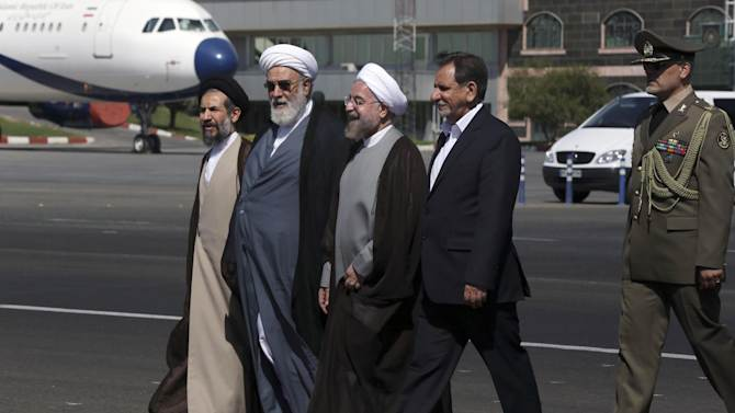 Iranian President Hassan Rouhani, center, is seen off by Vice-President Eshagh Jahangiri, second right, the head of the supreme leader's office, Mohammad Mohammadi Golpayegani, second left, and deputy parliament speaker Mohammad Hassan Aboutorabi Fard, left, during an official departure ceremony as he leaves Mehrabad airport in Tehran, Iran, en route to New York to attend the United Nations General Assembly, Monday, Sept. 22, 2014. As world leaders gather at the U.N. this week, the U.S. and its European allies are consumed by efforts to blunt the savage advance of the Islamic State group, to end the raging Ebola epidemic and to make progress in nuclear negotiations with Iran. (AP Photo/Vahid Salemi)
