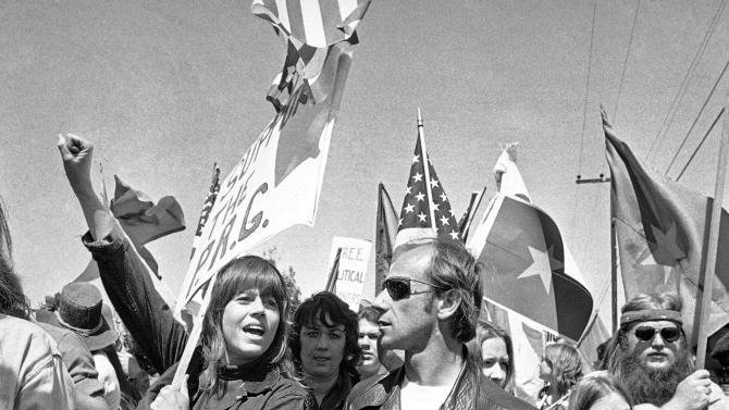 "FILE - In this April 2, 1973 file photo, actress Jane Fonda holds her arm up in the air as she joins a group of anti-war demonstrators on a march toward the Western White House to protest the visit of South Vietnam's President Nguyen Van Thieu in San Clemente, Calif. Jane Fonda says she's been banished from QVC amid concerns about her political past. The network says it was a routine programming change. Fonda was set to appear on the home-shopping channel on Saturday, July 16, 2011 to promote her new book on aging, ""Prime Time."" But the day before, she learned her segment had been canceled. (AP Photo/Harold Filan, File)"
