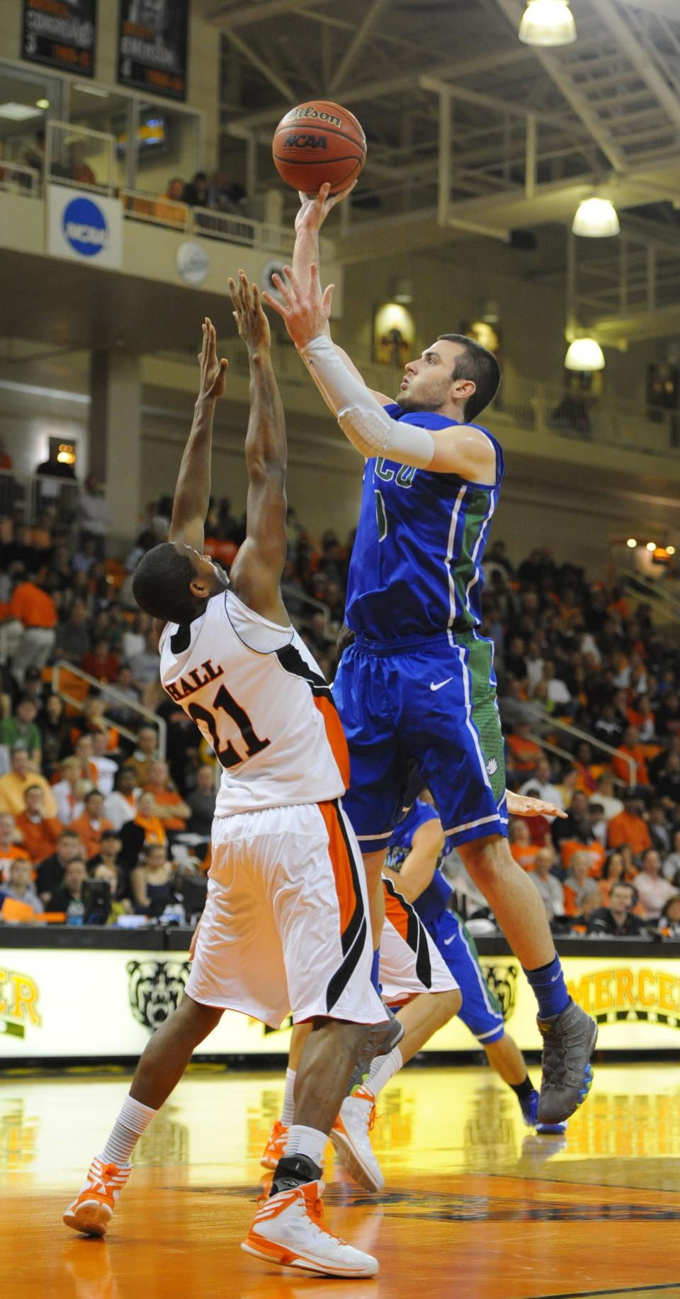 Mercer's Langston Hall (21) defends Florida Gulf Coast's Brett Comer during the first half of an NCAA college basketball game for the Atlantic Sun men's tournament championship in Macon, Ga., Saturday, March 9, 2013. Florida Gulf Coast won 88-75. (AP Photo/Woody Marshall)