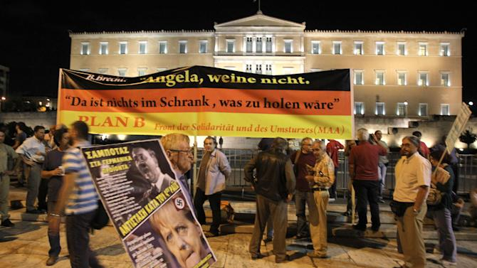 """Protestors holding banners protest outside the Greek Parliament in Athens Oct. 8, 2012 during an union anti-austerity rally a day before the visit by German Chancellor Angela Merkel. The authorities are keen to prevent embarrassing riots. More than 7,000 police will be on security duty in the capital from early Tuesday, while public gatherings will be banned in much of the city center and on a 100-meter (yard) radius from the route her motorcade will follow. The ban will not affect the main protests, but will prevent demonstrators from reaching the German embassy, where a populist right wing party was planning a protest. Banners read """"Merkel don't cry"""", """"Sabotage to the German products"""" and """"resist against the 4th Reich.""""(AP Photo/Thanassis Stavrakis)"""