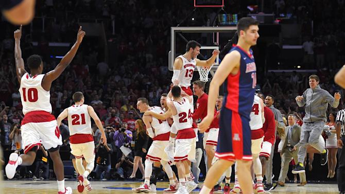 Wisconsin players celebrate as Arizona's Dusan Ristic walks off the court after Wisconsin defeated Arizona 85-78 in a regional final to advance to the Final Four in the NCAA men's college basketball tournament, Saturday, March 28, 2015, in Los Angeles. (AP Photo/Mark J. Terrill)