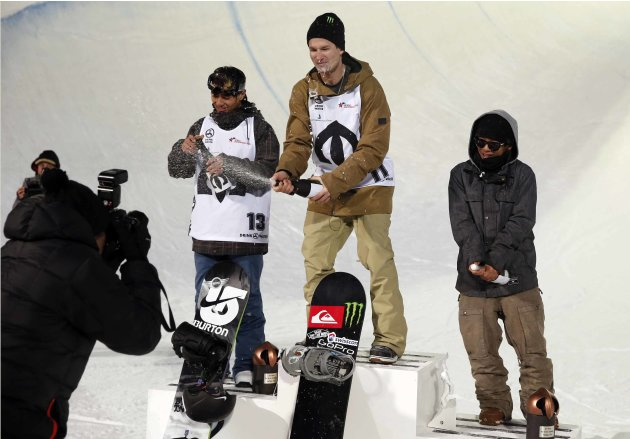 Winners celebrate on the podium after participating in the snowboard half-pipe competition during the Arctic Challenge at Oslo Winter Park near the Holmenkollen Ski Arena in Oslo