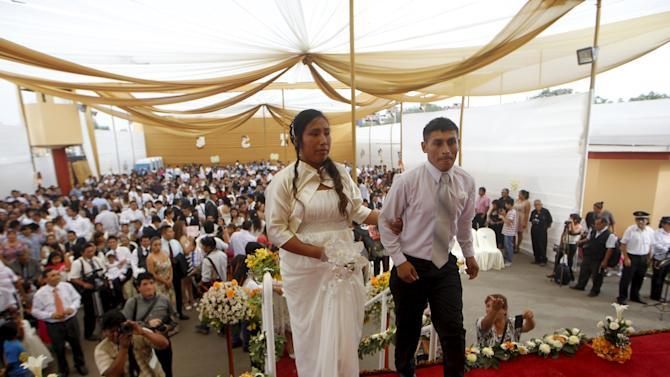 A couple walk to receive their marriage certificate during a mass wedding ceremony ahead of Valentine's Day celebrations in Lima