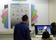 "Customers browse products in front of an Apple Ipad advertisement board at an Apple store in Beijing, February 2012. A Chinese computer firm involved in a legal battle with Apple over the iPad trademark said it is suing the technology giant in California for ""unfair business and fraud."""