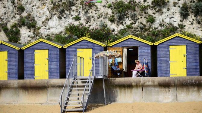 A woman and her dog sit outside their beach hut as they enjoy the sun in Broadstairs
