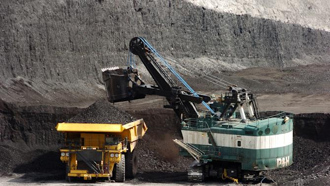In this April 4, 2013 photo, a mechanized shovel loads a haul truck that can carry up to 250 tons of coal at the Spring Creek coal mine near Decker, Mont.  From the time coal is blasted from strip mines in remote southeastern Montana to the point where it reaches customers in Asia, the fuel's price gets marked up by five times or more, offering a lucrative emerging market for the companies that ship it overseas. But as the federal government investigates whether companies are unfairly bilking the treasury by paying royalties based on a far lower coal price, one of the industry's main players, Cloud Peak Energy, is defending the practice.  (AP Photo/Matthew Brown)