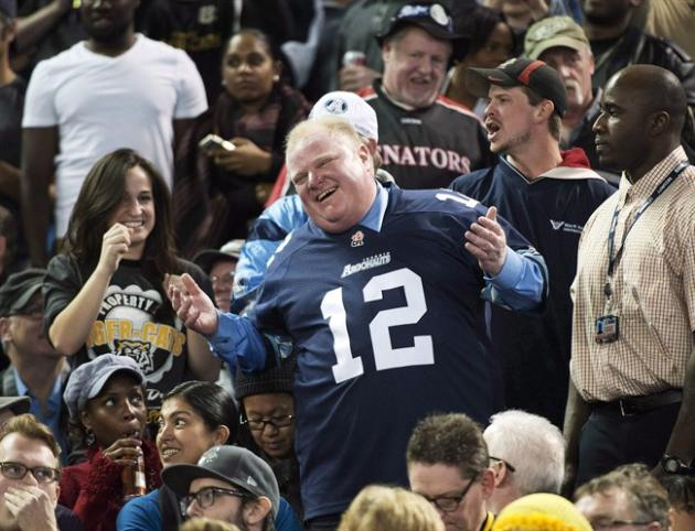 Toronto Mayor Rob Ford laughs with fans as he attends the Toronto Argonauts and Hamilton Tiger-Cats CFL Eastern Conference final football game in Toronto on Sunday, Nov. 17, 2013. A quartet of self-de