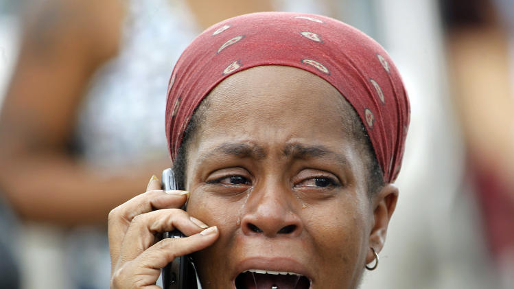 Nicole Webb cries as she talks on a phone in the parking lot of a store while waiting for her 9-year-old son, a student at Ronald E. McNair Discovery Learning Academy in Decatur, Ga., on Tuesday, Aug. 20, 2013. Superintendent Michael Thurmond says all students at the school east of Atlanta are accounted for and safe and that he is not aware of any injuries. (AP Photo/John Bazemore)