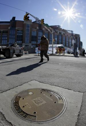 In this Jan. 28, 2012 photo, a pedestrian passes by a manhole cover outside Lucas Oil Stadium in Indianapolis. Indianapolis Power & Light has spent nearly $200,000 to replace 150 manhole covers in the Super Bowl Village and in other areas expected to draw high pre-game traffic after a series of underground explosions last year turned the covers into dangerous projectiles that damaged cars. (AP Photo/Mark Humphrey)