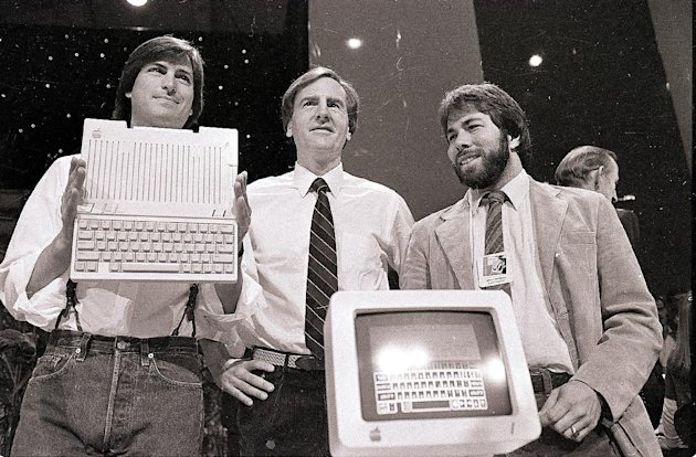 FILE - In this April 24, 1984, file photo, from left, Steve Jobs, chairman of Apple Computers, John Sculley, president and CEO, and Steve Wozniak, co-founder of Apple, unveil the new Apple IIc compute