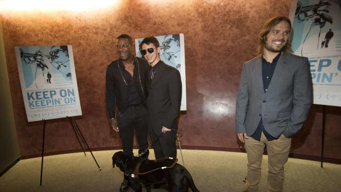 "Pianist and cast member Justin Kauflin and his seeing eye dog Candy pose with Chris Tucker standing near director Alan Hicks at the premiere of the documentary ""Keep on Keepin' On"" in Los Angeles"
