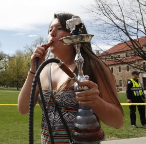 A student uses a water pipe to smoke marijuana outside the police barrier on the Norlin Quad at the University of Colorado in Boulder, Colo., on Friday, April 20, 2012. Police blocked off the quad to prevent a 420 marijuana smoke out. (AP Photo/Ed Andrieski)