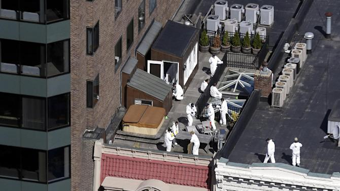FILE - Investigators inspect the roofs of buildings in Boston on Thursday, April 18, 2013 adjacent to the area where a bomb exploded near the Boston Marathon finish line. (AP Photo/Julio Cortez)