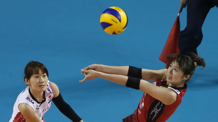 Kimura of Japan receives the ball next to Sano during their FIVB Women's Volleyball World Grand Prix 2014 final round match against Belgium in Tokyo