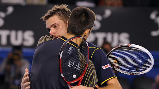 Serbia's Novak Djokovic embraces Switzerland's Stanislas Wawrinka, facing camera,  after Djokovic won their fourth round match at the Australian Open tennis championship in Melbourne, Australia, Sunday, Jan. 20, 2013.  (AP Photo/Andrew Brownbill)