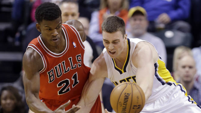 Chicago Bulls forward Jimmy Butler, left, knocks the ball away from Indiana Pacers forward Tyler Hansbrough during the first half of an NBA basketball game in Indianapolis, Monday, Feb. 4, 2013. (AP Photo/Michael Conroy)