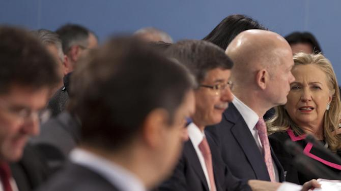 U.S. Secretary of State Hillary Clinton, right, speaks with British Foreign Minister William Hague, second right, during a meeting of NATO foreign ministers at NATO headquarters in Brussels on Tuesday, Dec. 4, 2012. NATO foreign ministers are expected to approve Turkey's request for Patriot anti-missile systems to bolster its defense against possible strikes from neighboring Syria. (AP Photo/Virginia Mayo)