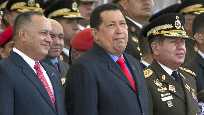 FILE - In this June 24, 2012 file photo, National Assembly President Diosdado Cabello, left, President Hugo Chavez, center, and Defense Minister Gen. Henry Rangel attend a military parade at the military academy in Fuerte Tiuna, Caracas, Venezuela. With Chavez now knocked low by a stubborn cancer and the future of his government in question, the armed forces may not be so prepared to hold the country together this time. A former military officer and several experts said the president's five-week absence has created a gaping hole at the top of the chain of command, one that the governing duo of Vice President Nicolas Maduro and National Assembly President Diosdado Cabello has proven incapable of filling. (AP Photo/Ariana Cubillos, File)