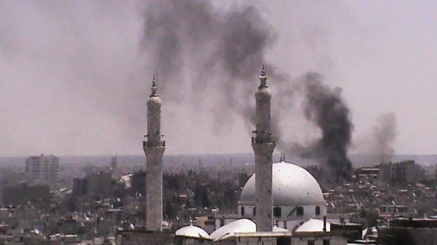 In this citizen journalism image provided by Shaam News Network SNN, taken on Wednesday, July 11, 2012, black smoke rises from buildings near a mosque from purported forces shelling in Homs, Syria. (AP Photo/Shaam News Network, SNN)THE ASSOCIATED PRESS IS UNABLE TO INDEPENDENTLY VERIFY THE AUTHENTICITY, CONTENT, LOCATION OR DATE OF THIS CITIZEN JOURNALIST IMAGE