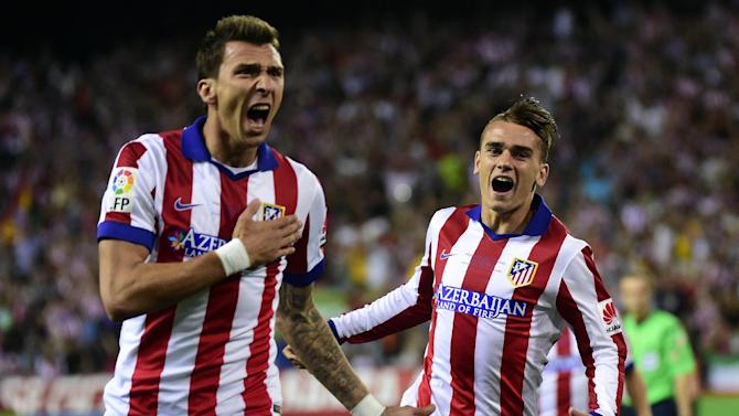 Atletico Madrid's Mario Mandzukic (L) celebrates with teammate Antoine Griezmann after scoring during the La Liga match against Real Madrid in Madrid on August 22, 2014