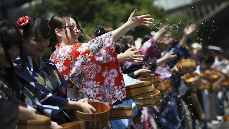 People wearing yukata, or summer kimono, sprinkle water on a street during an annual summer event at Akihabara electronics shopping district in Tokyo Saturday, Aug. 2, 2014. The event is to encourage people to get over hot summer. (AP Photo/Eugene Hoshiko)