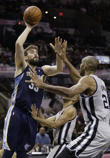 Memphis Grizzlies' Marc Gasol shoots the ball against San Antonio Spurs' Tony Parker, of France, and Tim Duncan, right, during the second half in Game 2 of the Western Conference finals NBA basketball