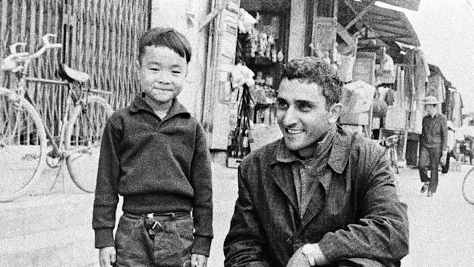 FILE - In this Jan. 1, 1966 file photo, AP special correspondent George Esper poses with a Vietnamese boy in Quang Ngai Province, south of Da Nang. The recent deaths of Esper, photographer Horst Faas, correspondent Malcolm Browne, and writer Roy Essoyan represent the slipping away of a generation of war reporters that brought the reality of the conflict to the living rooms of America in often horrifying close-up and inspired scores of combat journalists in their wake.  (AP Photo, file)