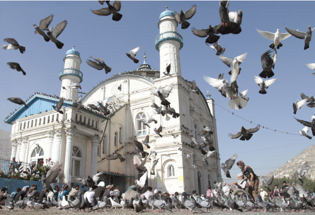 Pigeons fly outside Shah-e-Dushamshera's mosque where Afghans offer the Eid al-Fitr's prayers that marks the end of holy fasting month of Ramadan in Kabul, Afghanistan, Sunday, Aug. 19, 2012. (AP Phot