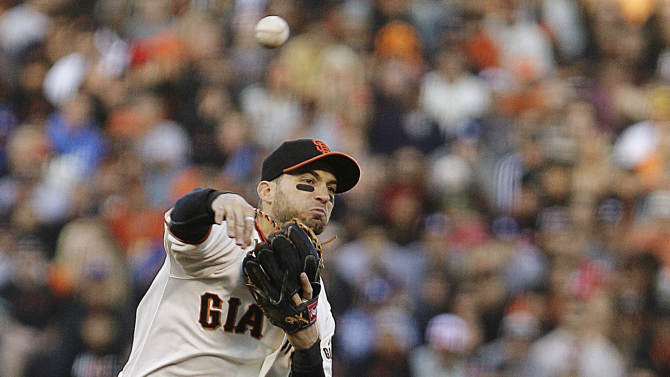 San Francisco Giants second baseman Marco Scutaro, left, throws to first base over Los Angeles Dodgers' Juan Rivera in the fifth inning of a baseball game, Sunday, Sept. 9, 2012, in San Francisco. Rivera was out on the play, and A.J. Ellis was safe at first base. (AP Photo/Ben Margot)