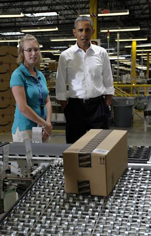 President Barack Obama, accompanied by Adrienne Thompson, tours the Amazon fulfillment center in Chattanooga, Tenn., Tuesday, July 30, 2013. Obama came to Chattanooga to give the first in a series of policy speeches on his proposals for private sector job growth and to strengthen the manufacturing sector. (AP Photo/Susan Walsh)
