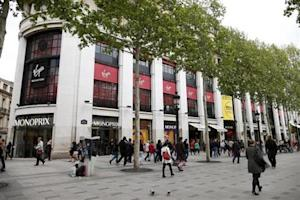 People walk near the Virgin Megastore building on the Champs Elysees in Paris