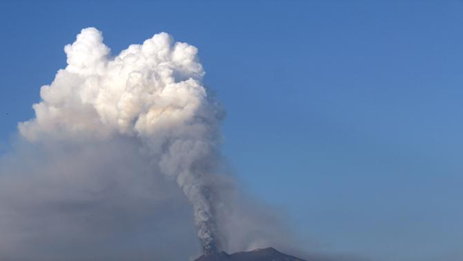 Smoke billows during an eruption of Mount Etna volcano as seen from the village of Viagrande, near the Sicilian town of Catania, Italy, Saturday, Oct. 26, 2013. Mount Etna, Europe's most active volcano, has erupted, sending up a towering plume of ash visible in much of eastern Sicily. Etna's eruptions are not infrequent, although the last major one occurred in 1992. Catania airport said the eruption Saturday forced closure of nearby air space before dawn, but authorities lifted the closure in early morning. Several inhabited villages dot the mountain's slopes, but evacuations weren't necessary despite the lava flow. (AP Photo/Carmelo Imbesi)