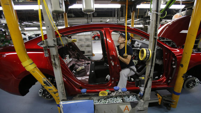 A Mazda employee works on the assembly line of the Mazda6 (Atenza) model at its plant in Hofu, Yamaguchi prefecture, southwestern Japan, Tuesday, Aug. 27, 2013. Mazda, the longtime also-ran of Japanese automakers, shows a new super-efficient plant that's rolling off vehicles at a stunning rate of one every 54 seconds. The plant is part of the reason why Mazda Motor Corp. has managed to defy skeptics who've predicted fates ranging from bankruptcy to a buyout by Chinese interests. (AP Photo/Shizuo Kambayashi)