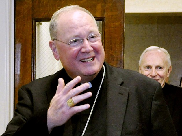 FILE - In this March 12, 2012 file photo, Cardinal Timothy Dolan leaves a meeting at the New York State Capitol in Albany, N.Y. Dolan says he's now giving the closing prayer at both the Democratic and Republican conventions. The New York Roman Catholic leader made the announcement Tuesday through his spokesman. (AP Photo/Stewart Cairns, File)