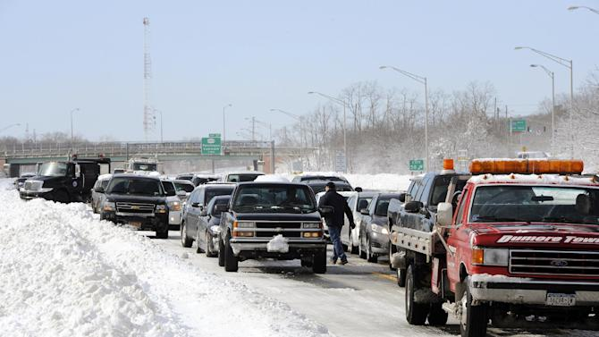 Traffic is backed up on the Long Island Expressway just west of Exit 59 Ocean Avenue as payloaders clear snow from the road after a storm, Saturday, Feb. 9, 2013, in Ronkonkoma , N.Y. (AP Photo/Kathy Kmonicek)