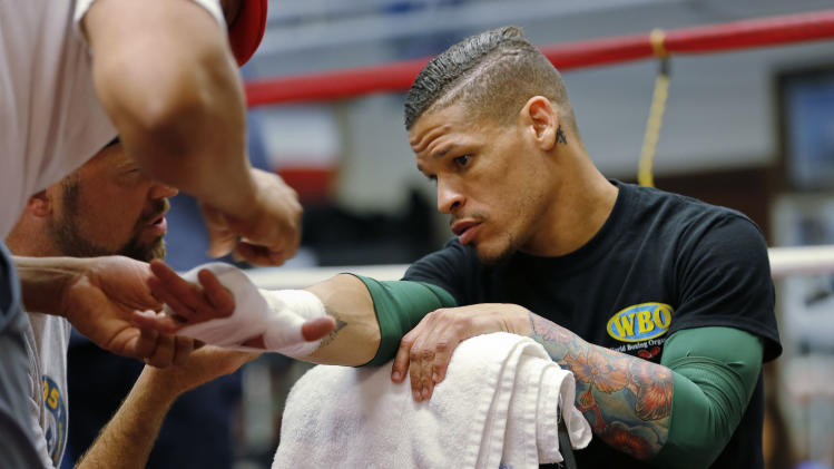 FILE - In this Sept. 24, 2013 file photo, boxer Orlando Cruz has his hands wrapped before a workout at Mendez Boxing Gym, in New York. Cruz won the big fight of his life outside the ring when he came out as the first openly gay boxer. Now he fights for a championship Saturday night, Oct. 12, in the biggest fight of his boxing career.(AP Photo/Nat Castaneda, File)