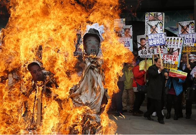 South Korean protesters burn effigies of North Korean leader Kim Jong-Un, and late leaders Kim Jong Il and Kim Il Sung at an anti-North Korea protest on the birthday of Kim Il Sung in Seoul, South Kor