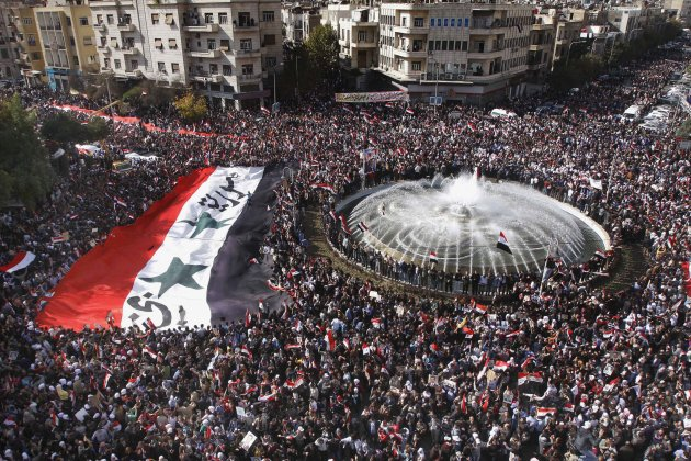 Pro-Syrian regime protesters, carry a giant Syrian flag during a demonstration against the Arab League decision to suspend Syria, in Damascus, Syria, on Sunday Nov. 13, 2011. Tens of thousands of pro-