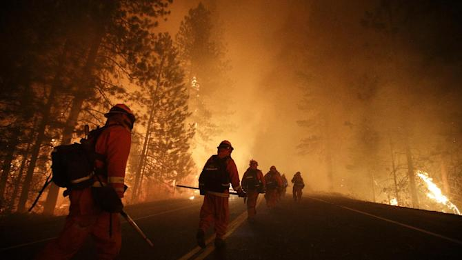 Inmate firefighters walk along Highway 120 as firefighters continue to battle the Rim Fire near Yosemite National Park, Calif., on Sunday, Aug. 25, 2013. Fire crews are clearing brush and setting sprinklers to protect two groves of giant sequoias as a massive week-old wildfire rages along the remote northwest edge of Yosemite National Park. (AP Photo/Jae C. Hong)