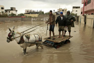 Palestinians help a man on their donkey cart to make their way in flooded water in Rafah? southern Gaza Strip, Wednesday, Jan. 9, 2013. In Gaza, civil defense spokesman Mohammed al-Haj Yousef said storms have cut electricity powering thousands of homes and rescuers were sent to evacuate dozens of people. (AP Photo/Eyad Baba)