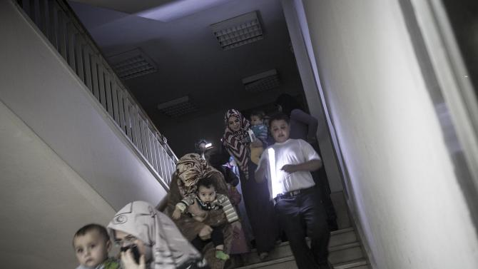 In this Friday, Nov. 02, 2012 photo, Syrian residents run for cover to an underground basement as an attack by Syrian army heavy artillery hits an apartment compound of rebel fighter's families in Aleppo, Syria. U.N. officials and human rights groups believe President Bashar Assad's regime is responsible for the bulk of suspected war crimes in Syria's 19-month-old conflict, which began as a largely peaceful uprising but has transformed into a brutal civil war.  However a video that appears to show a unit of Syrian rebels kicking terrified, captured soldiers and then executing them with machine guns raised concerns Friday about rebel brutality at a time when the United States is making its strongest push yet to forge an opposition movement it can work with. (AP Photo/Narciso Contreras)